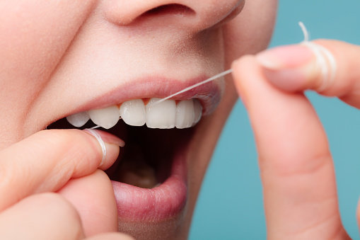 Bradshaw Family Dental patient flossing to avoid gum recession